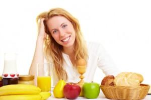 Blonde Frau sitzt lachend am Frühstückstisch